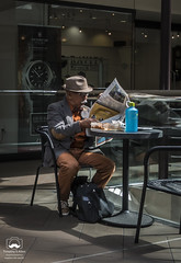 Taking Time for Lunch (allentimothy1947) Tags: architechure art califonia city crockergalleria exhibitioncatagories sanfrancisco buildings interior interiors landscape people man eating lunch newspaper reading dapper hat waterbottle advertisement 50postst mall time culture