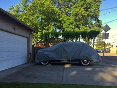 Awaiting The Great Unveiling (misterbigidea) Tags: hotwheels hobby living city bluesky spring green beauty urbansuburban streetview tree house yard driveway parked undercover covered coupe auto mystery garage treasure neighborhood vintage classic car ford 1946