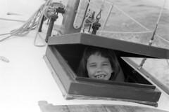 0403b68 09 (ndpa / s. lundeen, archivist) Tags: nick dewolf nickdewolf photographbynickdewolf april 1968 1960s bw blackwhite 35mm film monochrome blackandwhite neworleans louisiana nola sailing sailboat boat familyfriend johnsharp outing lake pontchartrain lakepontchartrain child girl nicole lifejacket lifepreserver smile smiling missingatooth hatch