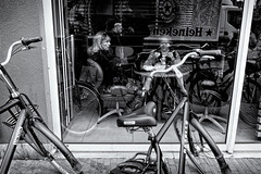 Me And The Rest In A Window (Alfred Grupstra) Tags: bicycle people urbanscene street blackandwhite citylife city outdoors editorial europe women oldfashioned retrostyled transportation cycling lifestyles travel cafe modeoftransport sitting