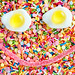 Flatlay of jelly fried eggs forming a smiley face and sprinkles textured background