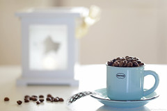 Coffee overdose... (eleni m, longing for spring...) Tags: coffee beans overdose tabletop cup saucer ribbon macro dof feather lantern windlight blue white brown yellow cream