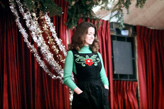 1a-765 (ndpa / s. lundeen, archivist) Tags: nick dewolf nickdewolf photographbynickdewolf 1978 1970s color 35mm film 1a reel1a aspen colorado fashionshow communityfashionshow socialevent people decorations curtains redcurtains model woman youngwoman turtleneck brunette longhair handsinpockets handsinherpockets pockets greenturtleneck dress