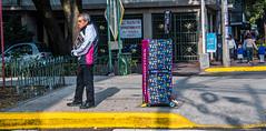 2018 - Mexico City - Máspormás (Ted's photos - For Me & You) Tags: 2018 cdmx cityofmexico cropped mexico mexicocity nikon nikond750 nikonfx tedmcgrath tedsphotos tedsphotosmexico vignetting curb yellow male man newspapers vendor maspormas máspormás railing fencing streetscene people peopleandpaths shadow