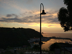 Cudillero port at sunset (Alejandro Hernández Valbuena) Tags: cudillero spain town architecture asturias building cantabrico coast europe harbor home house night ocean outdoor picturesque port roof rural small orange sunset lamppost sea