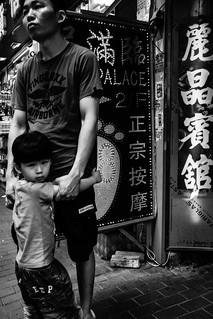 Father and son standing behind the signboard of love hotel