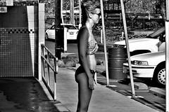 Sun comes out (thomasgorman1) Tags: woman beach water cars hawaii bikini sunglasses bw monochrome sunlight sunshine island standing street public candid swimwear streetphotos streetshots walkway