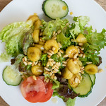 Salad with iceberg lettuce, tomato, cucumber, flambéed banana and pine nuts thumbnail