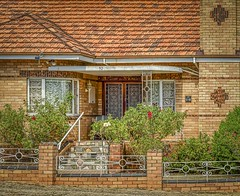 Castlemaine VIC (phunnyfotos) Tags: phunnyfotos australia victoria vic centralvictoria castlemaine house residence home brick wroughtiron porch front window curved curvedglass curvedwindow fence chimney garden crazypaving brickwork nikon frontdoor architecture tiledroof rooftiles d500 nikond500 details brickdetails