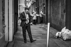 Business As Usual (Leanne Boulton) Tags: urban street candid portrait streetphotography candidstreetphotography streetlife urbanlandscape man male business businessman suit tie mobile phone standing posture juxtaposition grit grime dirty alley alleyway tone texture detail depthoffield bokeh naturallight outdoor light shade city scene human life living humanity society culture people canon canon5d 5dmkiii 70mm ef2470mmf28liiusm black white blackwhite bw mono blackandwhite monochrome glasgow scotland uk