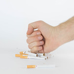 Close-up man hand crushing a pile of cigarettes thumbnail