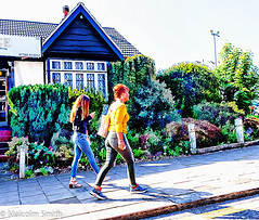 Modern Communication 11 (M C Smith) Tags: woman girl walking pentax k3 phone pavement buildings yellow red kerb shadows green plants hedge post chain numbers letters shadow steps lamp blue grey