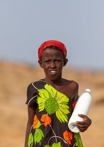 A nomad girl carrying a bottle of camel milk in the desert, Awdal region, Zeila, Somaliland