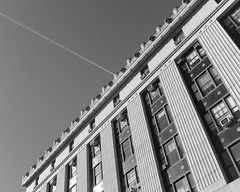 Contrail at 80 Centre Street on a Very Sunny Morning (Zach K) Tags: architect architecture nyc new york city civic center area office building da lefkowitiz stone masonry granite clerk contrail airplane jet angle sunny morning daylight harsh light fujifilm fuji x100f manhattan lower lowermanhattan justice bw black white
