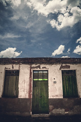Green door and windows in a vintage grunge abandoned exterior of a old house, in a blue sky with clouds sunny day. (pedroferr) Tags: ancient historic home southamerica structure door grunge architecture wall wood broken building concrete light old city vertical facade vintage rural aged poor texture bluesky exterior retro urban classic ruins brazil cloud house destroyed window green clouds abandoned rustic antique