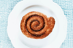 Top view of cinnamon roll in white plate. (wuestenigel) Tags: spice bake dessert recipe breakfast brown round healthy swirl rolls food homemade golden spiral isolated white view cinnamon bun closeup pastries dough tasty gourmet baked nutrition fresh traditional roll background top sweet crust bakery bread snack pastry delicious