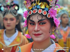 2018-02a Bangkok Chinatown (58) (Matt Hahnewald) Tags: matthahnewaldphotography facingtheworld aesthetic springfestival chinesenewyear parade performer dancer makeup lunaryear festival head face painted eyes costume consent fun entertainment travel tourism culture tradition enjoyment socialevent diversity impact traditional cultural folklore touristattraction celebration historical yaowarat bangkok chinatown thailand thaichinese asia photo physiognomy nikond3100 primelens 50mm 4x3 horizontal street portrait closeup outdoor color colorful iconic awesome incredible authentic sightseeing partying photography ambiguity attire headgear softfocus character relationship tripleportrait smallgroup headshot lifestyle posingcamera lookingcamera