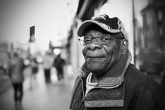 IMG_8469m (JetBlakInk) Tags: portrait empirewindrush pov pointofview naturallight face westindian afrocaribbean seniorcitizen streetphotography perspective enigmatic enigmaticsmile blackman windrushsquare brixton