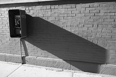 the long shadow of the 20th century (KevinIrvineChi) Tags: monochromemonday monochrome noir et blanc blanca blackwhite blackandwhite bnw bw payphone pay phone telephonoe telefono telephone bell wall brick shadow long 20th century 20thcentury chicago albanypark illinois sony dscrx100