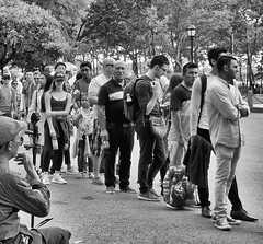 Standing in Line (Demmer S) Tags: eyecontact candideyecontact gathering crowd line crowds standing walking outdoors group documentary journalism reporter photographer street streetphotography people pedestrian peoplewatching shootthestreet streetlife streetshots candid candidstreet citylife person urban city outside urbanphotography streetscene urbanexploration waterfront harbor seaside esplanade summer summertime visitors tourists staredown whatareyoudoing downtownmanhattan tourist downtownnewyork lowermanhattan financialdistrict manhattan batterypark batteryparkcity thebattery park ny newyork nyc newyorkcity bw monochrome blackwhite blackandwhite trees lines blackwhitephotos blackwhitephoto pavement