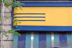Yellow and Blue, Bring Me Back To You (Gay Foster) Tags: marquee bright horizontal lines vertical village illinois street awning foster gay dirt pipes gaynell