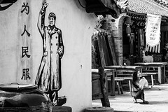The lady, the dog and... Mao (Go-tea 郭天) Tags: qingdao huangdao cangmashan ancient town village traditional tradition old house building construction history historical historic flags painting wall chairman mao communist leader leadership party famous sun sunny shadow young lady woman dog little animal love united together canon eos 100d 50mm prime street urban city outside outdoor people candid bw bnw black white blackwhite blackandwhite monochrome naturallight natural light asia asian china chinese shandong