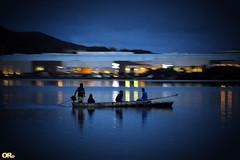Night boating (Otacílio Rodrigues) Tags: canoa homens men navegando navegating sailing água water mar sea reflexos reflections luzes lights noite night prédio building shopping céu montanha cabofrio brasil oro canoe lagoa lagoon parklagos