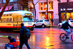 Market St Candids 50a (TheseusPhoto) Tags: people city street sanfrancisco california candid streetphotography color rain reflection wet streetcar trolley homeless bicycle blur