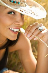 Stock Images (perfectionistreviews) Tags: color outdoors vertical caucasian onepersononly midadultwoman cowboyhat strawhat chewing gnawing straw lookingatviewer smiling rural country 3035years southwestern eyecontact portrait posed headandshoulders photograph smile people maui hawaii unitedstates