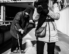 Street - Begging bowl versus mobile (François Escriva) Tags: street streetphotography paris france candid olympus omd people man woman hat beggar begging bowl sun light building mobile cell black white bw noir blanc nb monochrome photo rue bag defense