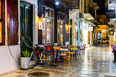 Taste of Navplion (George Plakides) Tags: navplion nafplion street wet rain evening dark lights bicycle flowers pots chairs tables