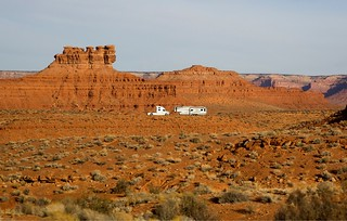 A white semi tractor truck and trailer camper RV parked alone in the desert landscape of southern Utah near Monument Valley