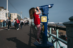 Telescope 152/156 (markfly1) Tags: little girl cute red top stripes lines blue cyan shadown sunlight sunny day spring street candid promenade people small cant reach stretching hanging funny sight nikon d750 35mm manual focus lens eye telescope beautiful