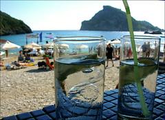view down another corfu bar (Ron Layters) Tags: blue sea beach bar digital geotagged straw gin umbrellas corfu tonic paleokastritsa viewdownthebar flickrfly ronlayters geo:lat=396733 geo:lon=197151 takenonronetscamera akronbeachcafe abiatriadabay