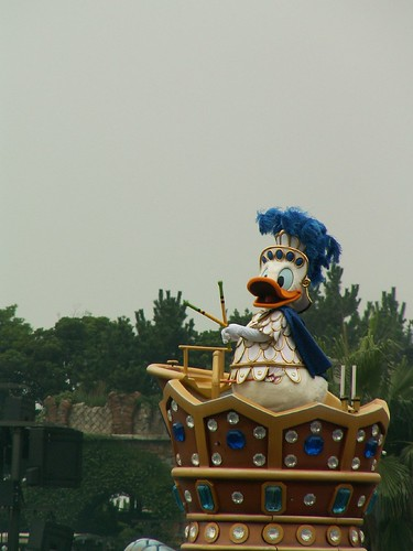 Donalds head dress blows in the wind as he beats his drum sticks.