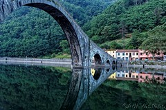 Ponte della Maddalena (detto anche del Diavolo) a Borgo a Mozzano (Lucca) (Fotografo per Diletto (The Original)) Tags: bridge water river tree nature building grass arch archbridge landscape architecture outdoors plant lake train outdoor track arched noperson travel reflection wood going pond fixedlink long flora devilsbridge suspensionbridge traveling scenic reservoir view old bank forest green tourism watercourse riding area large road black park field adi vastano ponte borgoamozzano