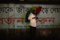 The RainBow Man (N A Y E E M) Tags: man umbrella colors rain monsoon night candid portrait light availablelight atmosphere street crbroad chittagong bangladesh carwindow sooc raw unedited untouched