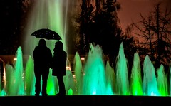 The shape of water 💖 (Christie : Colour & Light Collection) Tags: fountain silhouette couple contrast dancingwater evening night light water longexposure exposure dancingwaters nightphotography outdoors theshapeofwater green umbrellasilhouette umbrella rain love romance romantic tranquility quiet waters spring trees darkness nightfall rainynight springromance