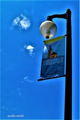 The face in the cloud watches over the town (Explore!) (SCOTTS WORLD) Tags: adventure america angle art july 2017 portaustin michigan midwest light lamppost banner bluesky clouds urban usa unitedstates urbanart urbanexploring panasonic pov perspective fun flag lighthouse outdoors outside