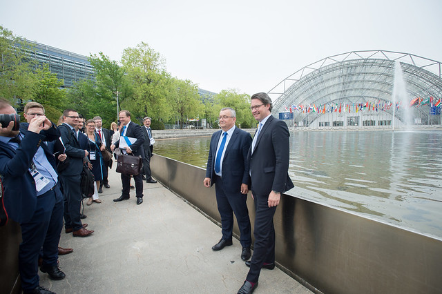Andrzej Adamczyk and Andreas Scheuer have their photo taken in front of the Conference Centre building
