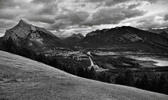 Banff View Point or One Heck of a View Across Banff with Views to Mount Rundle, Sulphur Mountain, and the Canadian Rockies (Black & White) (thor_mark ) Tags: nikond800e lookingsse day2 triptoalbertaandbritishcolumbia banffnationalpark capturenx2edited colorefexpro silverefexpro2 blackwhite banffviewpoint mountnorquayscenicdrive banff mountrundle vermillionlakes road mtnorquayrd goatviewpeak sansonpeak rockymountains canadianrockies southerncontinentalranges southbanffranges sulphurmountain rundlepeaks goatrange bowriver river intersection highwayintersection transcanadahighway transcanadahighway1 transcanadianhwy1 outside nature landscape overcast rollinghillsides mountains mountainsindistance mountainsoffindistance hillsides trees hillsideoftrees evergreens grassymeadow bowvalley citystreets street portfolio project365 alberta canada
