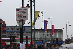 2018 04 10_7418 (djp3000) Tags: canoneosrebelt3i efs1855mmf3556isii tootingbroadway banners tooting london roadsigns trafficlight streetlamps streetlights lamppost bus