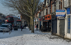 Station Road Snow 2 (M C Smith) Tags: shops pentax k3 bus red london chingford route 97 passengers people walking tables chairs snow trees orange black white signs bins cycle racks parking cars silver sky blue lamps busstop busshelter flowers metal shutters green pavement
