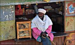 Ethiopian seller (gabi lombardo) Tags: man seller people venditore etiopia uomo bred pane bastone stock barba bart scritta beard turban merce ware chiosco kiosk rost ruggine rust inschrift äthiopien sitting rttratto portrait travel
