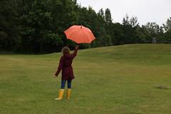 Enjoying the rain in color (liisatuulia) Tags: flickrfriday rainydaysand umbrella sateenvarjo raincoat boots kumisaappaat yellow orange green grass field finland helsinki