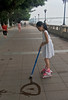 Little Street Painter (cowyeow) Tags: paint painting water waterpaint sidewalk pretty fun art artist young youth kids children cute guangzhou china people funny asia asian guangdong city composition travel street candid girl littlegirl child rollerblades urban