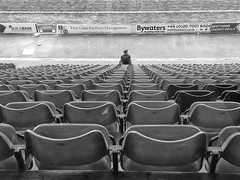 Billy No Mates (tcees) Tags: leytonorientfootballclub leyton e10 leytonorient urban bw mono monochrome blackandwhite seats rows man street adverts grass pitch tiers gate path iphone iphone5s eastlondon football footballground streetphotography allfreepicturesjuly2018challenge