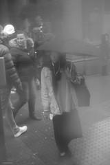 London Smog (Silver Machine) Tags: london streetphotography street candid girl umbrella rain busstop mist waiting standing umbrellas mono monochrome blackwhite bw fujifilm fujifilmxt10 fujinonxf35mmf2rwr