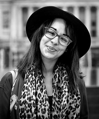 Lulu - stranger 147/200 (englishreader) Tags: 100strangers strangers strangerphotography stranger peoplephotography people streetportrait street streetphotography person portraitphotography portrait portraiture headshot female woman youngwoman lady younglady brunette hair longhair hat glasses scarf smile smiling happy thehumanfamily building buildings nottingham monochrome mono blackandwhite 50mmlens primelens canon daylight availablelight naturallight