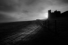 In The Shadow Of What's Gone Before (Julian Barker) Tags: dunstanburgh castle northumberland julian barker monocrome sun sunlight shadows north east england great britain uk europe history black white sky landscape fence mood atmosphere dark